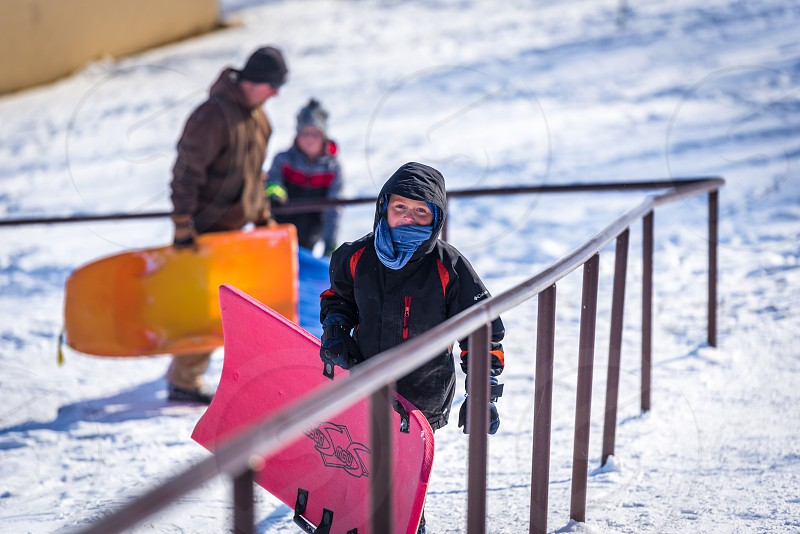 Kid walking up stairs in a park to go sledding in the winter time. photo