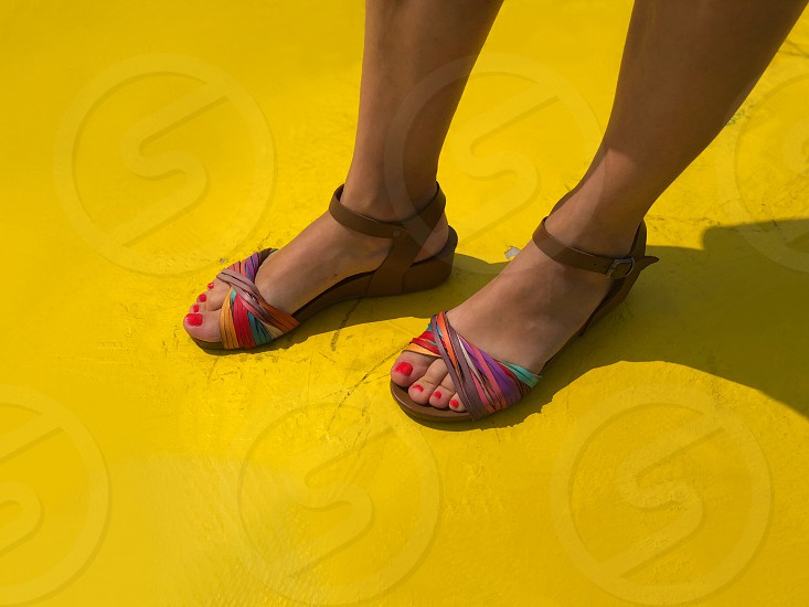 high angle view of woman's feet with colorful sandals on yellow background photo
