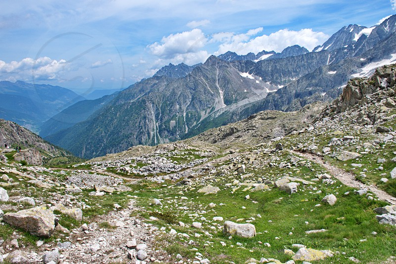 Meadow in Brenta Dolomites with rocks and mountains in the background photo