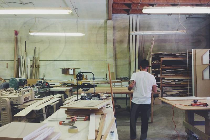 Drew & Sons wood shop making signage.  photo