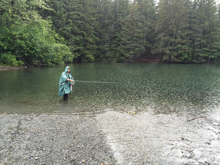 person wearing blue raincoat fishing in body of water beside green leaf trees under rain photo