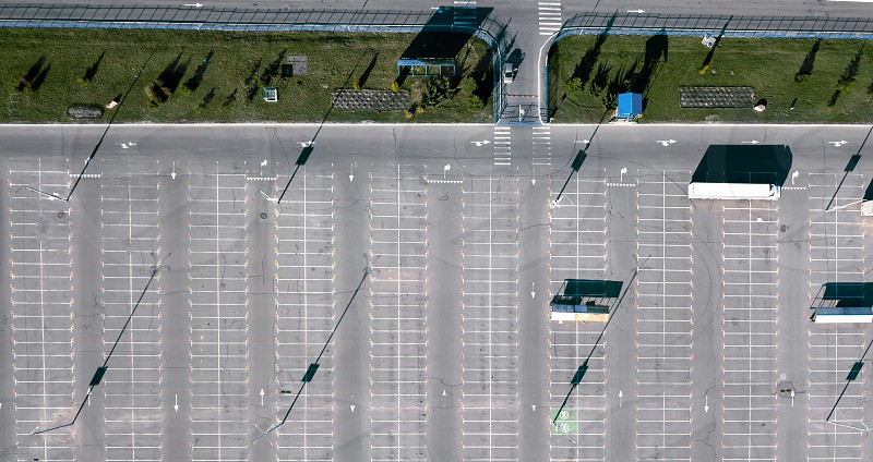 Aerial view from the drone of a truck in an empty parking lot next to a green lawn. Reflection of shadows from street lamps on the asphalt. Top view photo