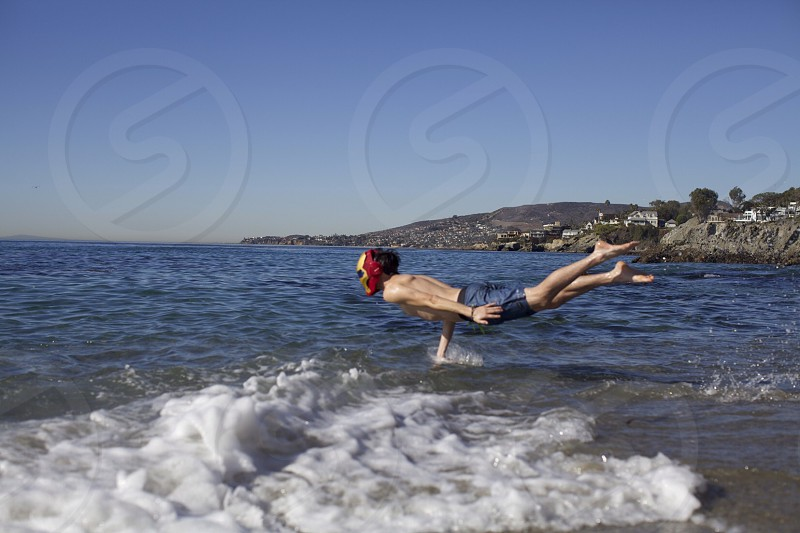 man wearing iron man mask jumping on the sea photo