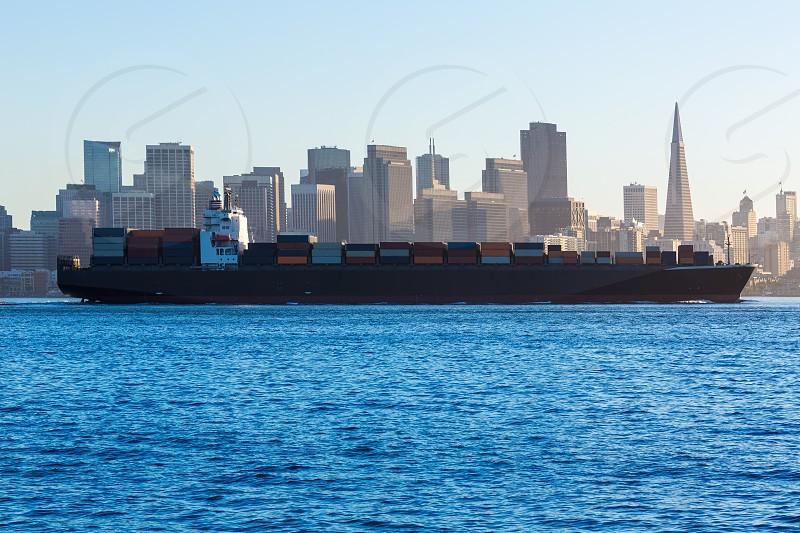 San Francisco Skyline with merchant ship cruising bay at California USA photo