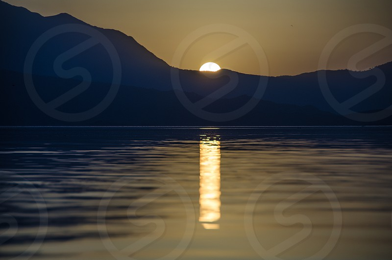 A mountain sunset reflected on the waters of a lake. photo