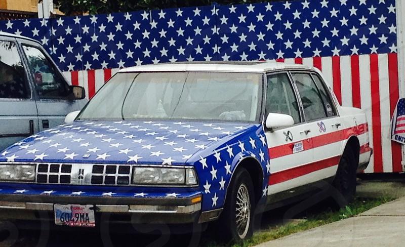 white sedan with us flag print photo