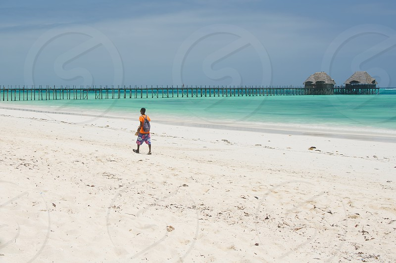 Man on white tropical beach of Zanzibar island - Tanzania - Africa photo