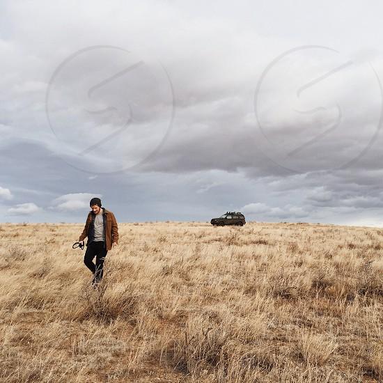 man in brown jacket walking on brown field near black SUV during daytime photo