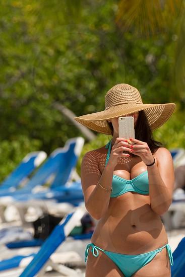 A beautiful woman in a bikini and sun hat on the beach taking a selfie photo