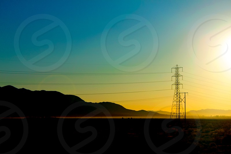 1 electric tower with 2 electric post on a bright sunny day photography photo