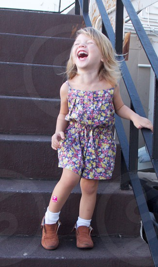 Llittle girl laughing as she walks down the stairs. photo