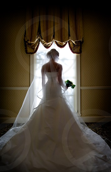 A bride holding a bouquet in front of a window photo
