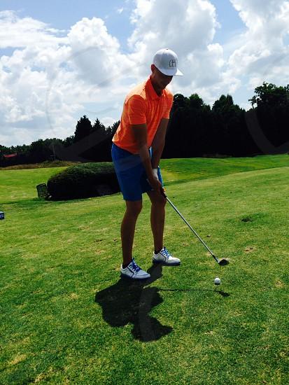 man in orange polo shirt playing golf during daylight photo