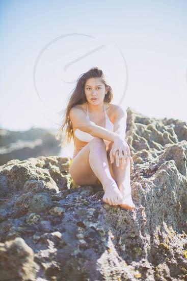 woman in bikini sitting on rock photo