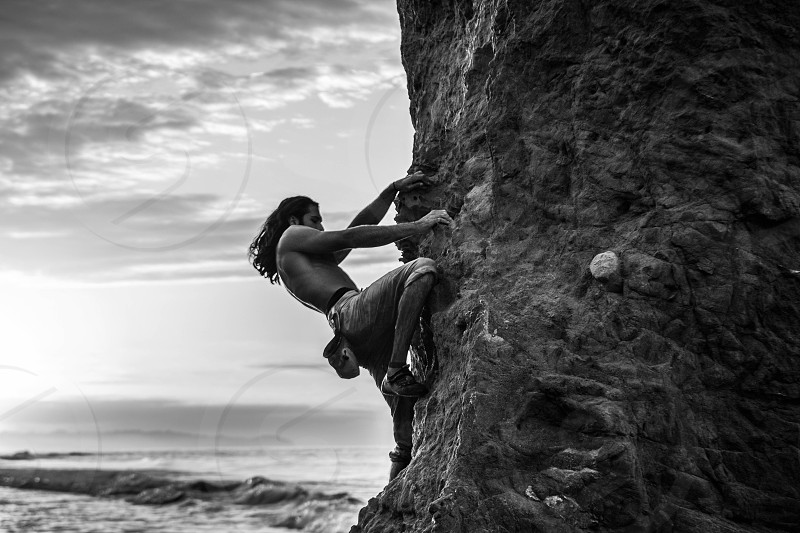grayscale photo of man climbing on rock formation photo