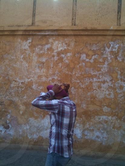 man wearing purple and white plaid dress shirt with purple turban near brown concrete wall photo