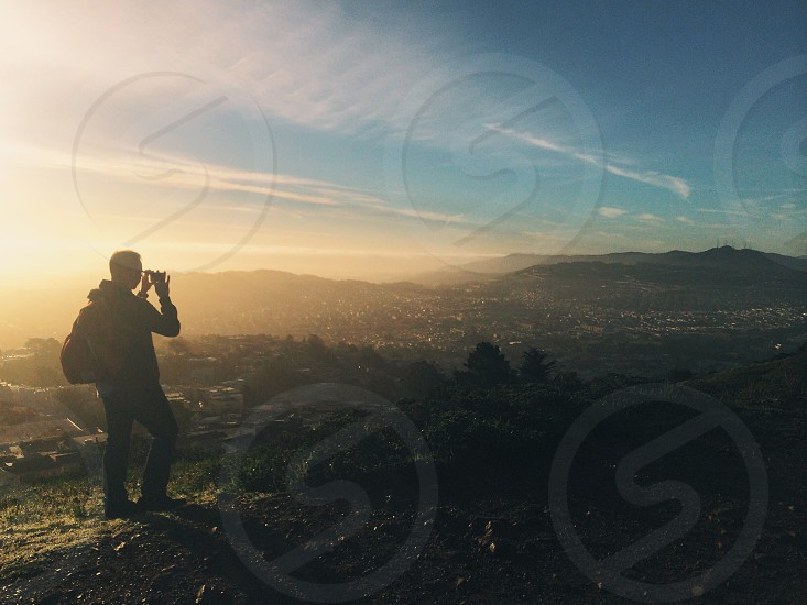 man on top of hill overlooking city lights during sunset photo