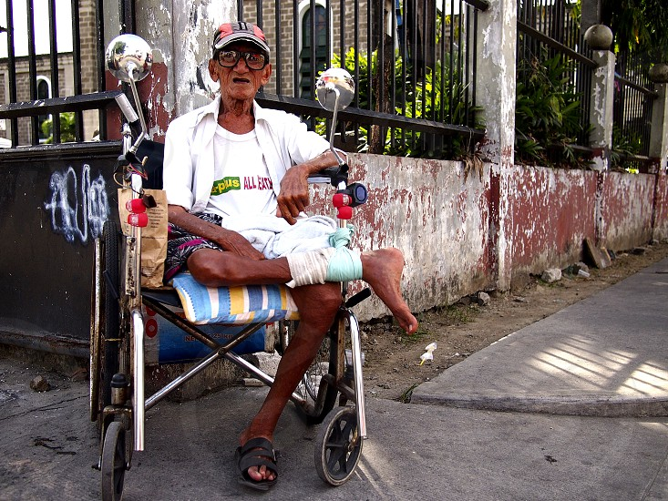 CAINTA RIZAL PHILIPPINES - JANUARY 17 2019: A man with disability sits in his wheelchair and looks at the camera. photo