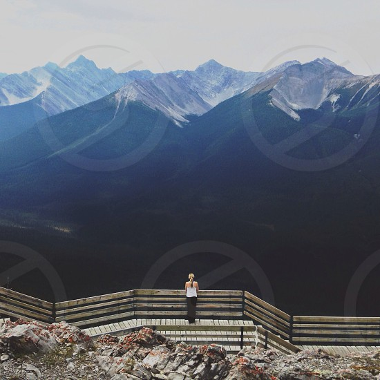 woman standing at a wooden fence overlooking mountains photo