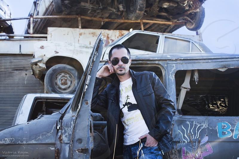 man wearing black zip jacket near wrecked grey car photo