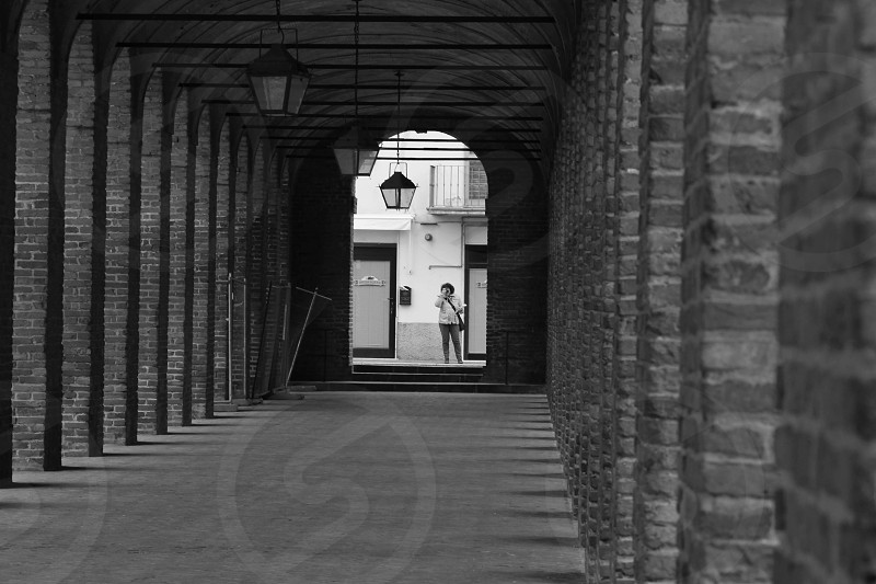 person standing at the end of archway photo