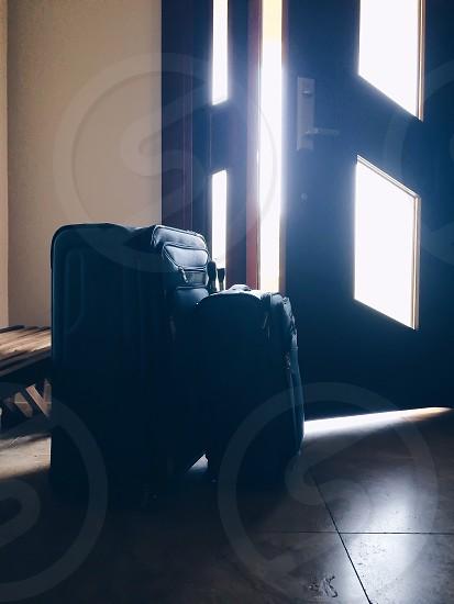 black luggage bag near brown wooden door photo