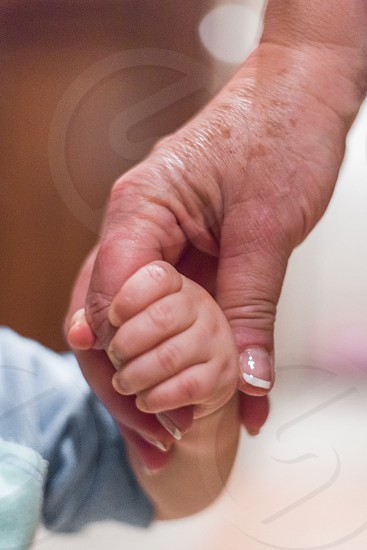 Close shot of a young child holding a grandmother's aged hand. photo