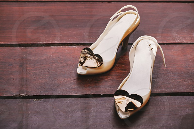Close-up shot of cute women's ivory pump shoes adorned with brushed heart decoration at the shoe head on the wooden floor with copy space on the left side photo