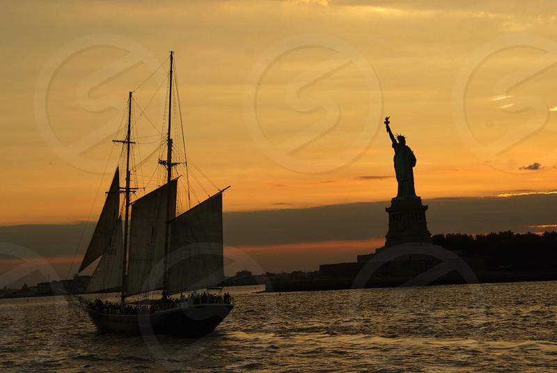 sailboat on water near statue of liberty photo