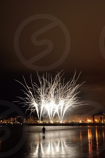 silhouette of person standing calm shallow water facing the white fireworks display over buildings at night photo