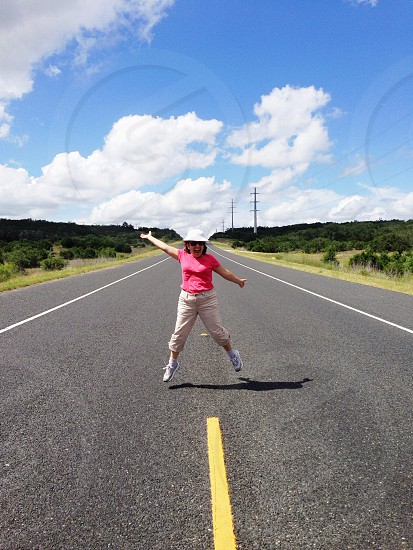 woman wearing pink t shirt standing on road photo