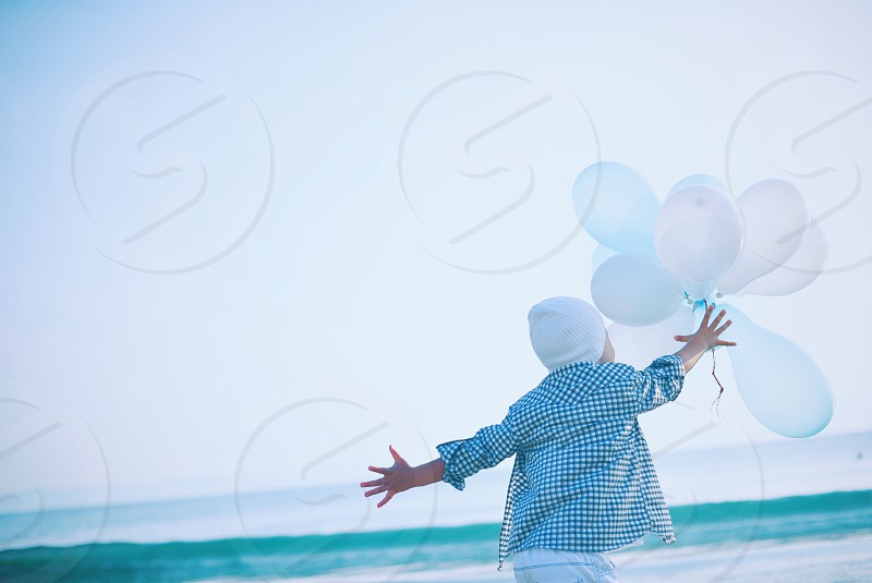 man in white and blue checkered button down t shirt holding white balloons during daytime photo