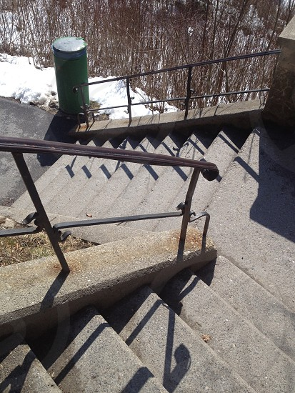 gray concrete stairs with brown metal handle bar railings photo