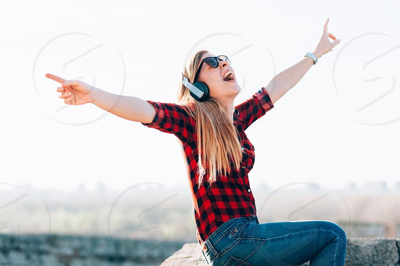 Young woman listening to the music on headphones outdoors photo