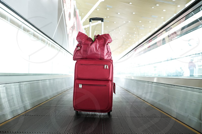 Red travel luggage on walkalator in an airport terminal building photo