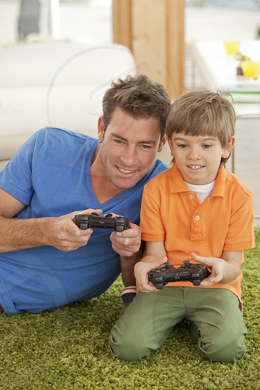 Portrait of loving young father and son playing video game at home photo