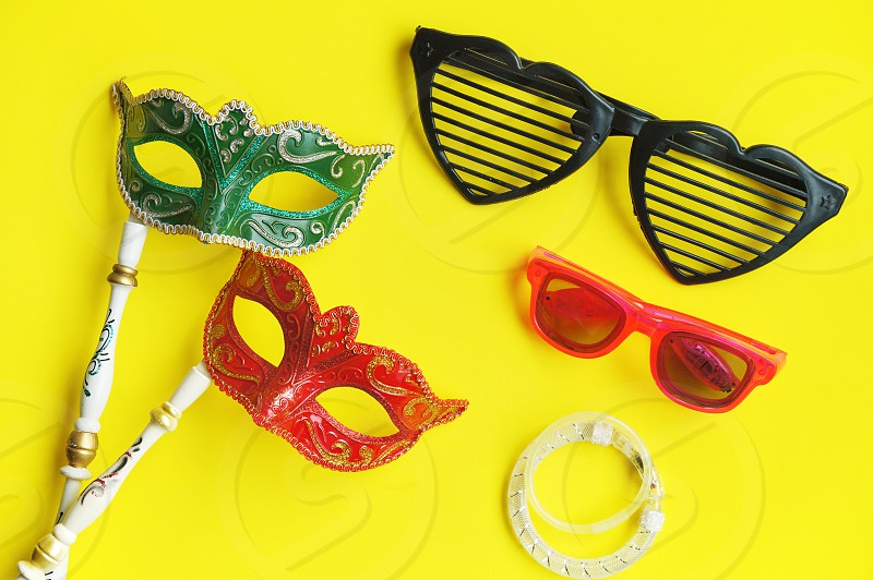 Carnival venetian masks in green and red with handle fancy glasses and glitter bracelets for photo booth isolated on vibrant yellow background Fancy mask with copy space photo