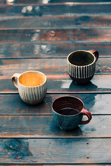 A couple of earthen cups with coffee and herbal tea on wooden wet table after rain photo
