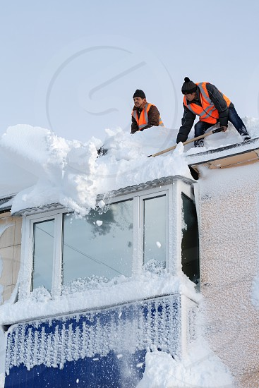 PETROPAVLOVSK CITY KAMCHATKA PENINSULA RUSSIA - DEC 27 2017: Workers in orange vests with snow shovels cleaning snow drifts from roof of high-rise building after bad weather (snowstorms blizzard) photo