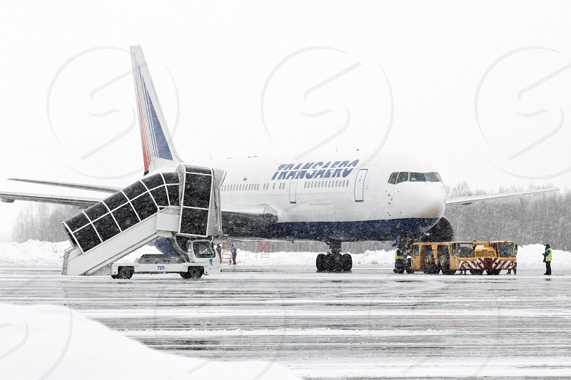 PETROPAVLOVSK-KAMCHATSKY KAMCHATKA RUSSIA - MARCH 19 2015: Passenger boarding bridge and airport trucks near airplane Boeing 767 Transaero Airlines at airport Petropavlovsk-Kamchatsky (Elizovo airport) during a snowfall and poor visibility. photo