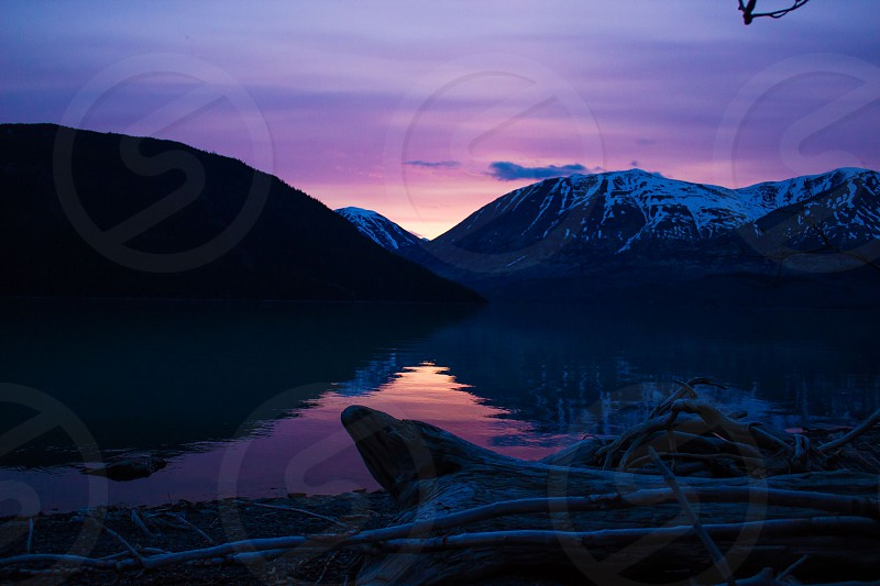 sunset over snowy mountain and lake view photo