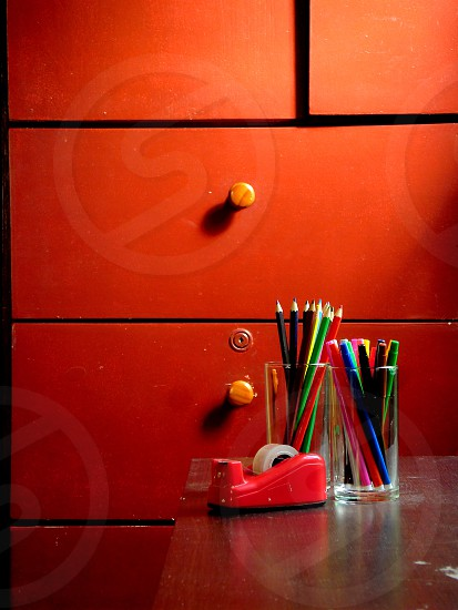 Different coloring materials on a table. color colorful colored coloring write writing art pens markers materials school paint painting sticky tape adhesive table wood wooden window cabinet door drawer  photo