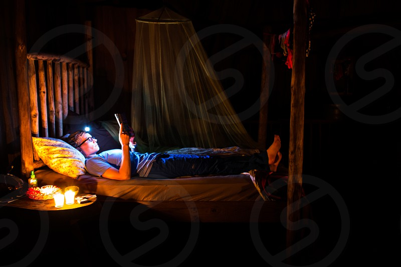 Woman doing some late night reading in a four post bed in a tree house in the jungle of Belize. photo