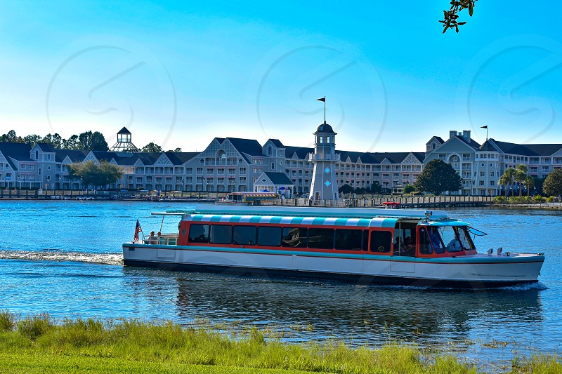 Orlando Florida. February 09 2019 Taxi boat sailing on lake with background of villas  and lighthouse at Lake Buena Vista area. photo