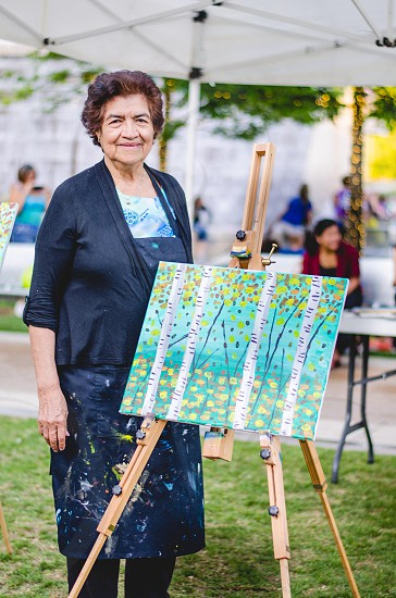 person with a tree designed painting at a brown wooden paintin stand photo