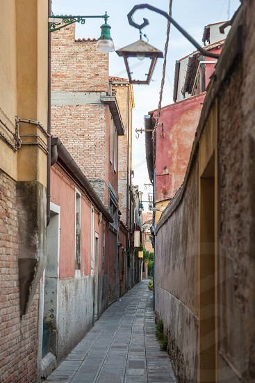Venetian buildings represented onnarrow street in Italy. Narrow road in Venice Italy. photo