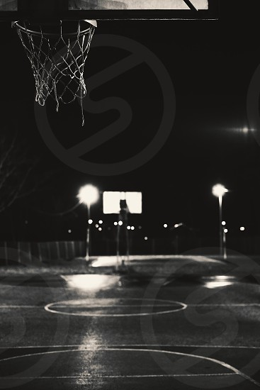 Emtpy basketball court by night details of hoop and terrain.  photo