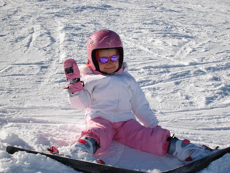 girl wearing pink helmet seated on snow field photo