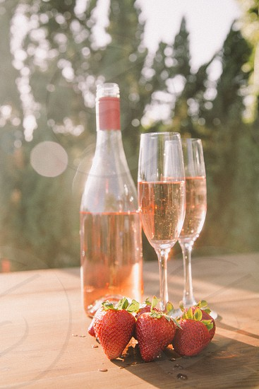 two champagne flutes filled with rose wine on a table with a wine bottle and strawberries photo