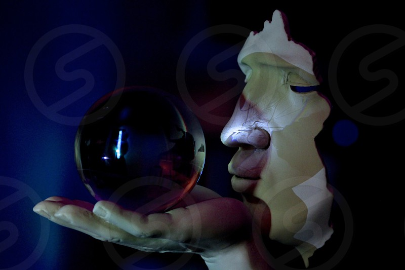 low-light photo of woman holding clear glass ball statuette photo